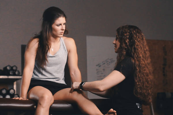 Dr. Jessica Rosi DPT with knee pain client sitting